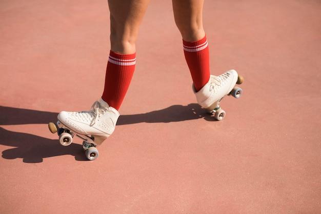 Lage sectie van een vrouw die op de rolschaats in evenwicht brengt
