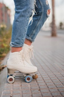 Lage sectie van een vrouwelijke skater in witte rolschaats die zich op stoep bevindt