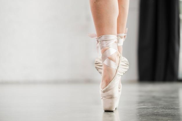 Lage sectie van het been van de ballerina in pointeschoenen die zich op vloer bevinden