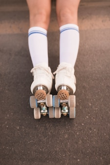 Lage sectie van het been van de vrouw die rolschaats op asfalt draagt