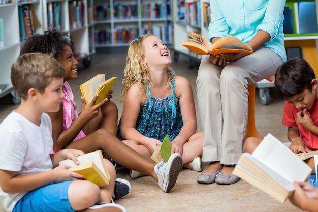 Lage sectie van leraar met kinderen die boeken lezen