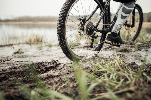 Lage sectie van mannelijke fietser berijdende fiets in modder