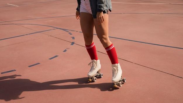Lage sectie van vrouw die op openluchthof schaatst