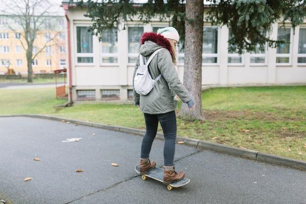Lage sectie van vrouw die op skateboard bij straat schaatsen