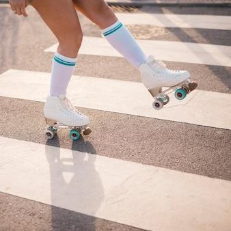 Lage sectie van vrouwelijke skater die op zebrapad schaatst