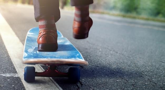 Lage sectie van zakenman die zijn lichaam op skateboard in park in evenwicht brengt