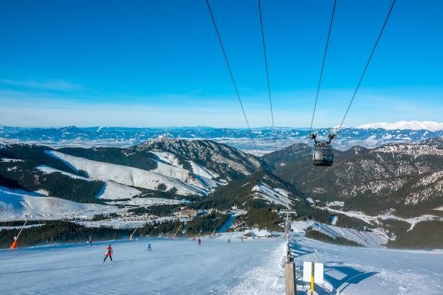 Lage tatra. slowaaks skigebied jasna bij zonnig weer. skipiste en liftcabine. blauwe lucht boven de bergtoppen