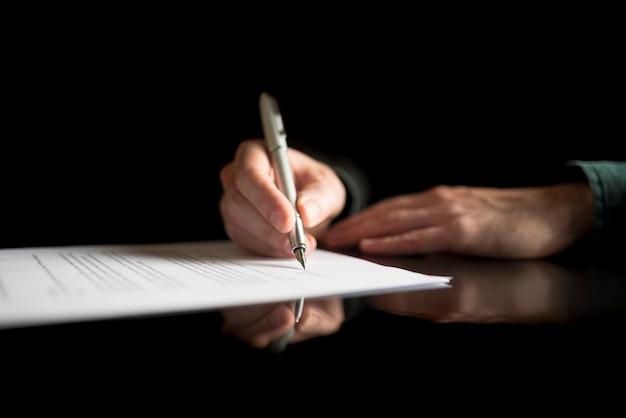 Lage weergave van zakenmanhand die juridisch of verzekeringsdocument of zakelijk contract ondertekent op zwart bureau met reflectie.
