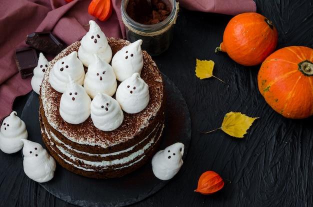 Lagen chocoladetaart met witte chocoladeroom en meringue geesten bovenop. voedselidee voor halloween-feest.