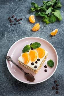 Lagen van biscuitgebak met botercrème, versierd met plakjes mandarijnchocolade en munt. heerlijk zoet dessert voor op de thee.