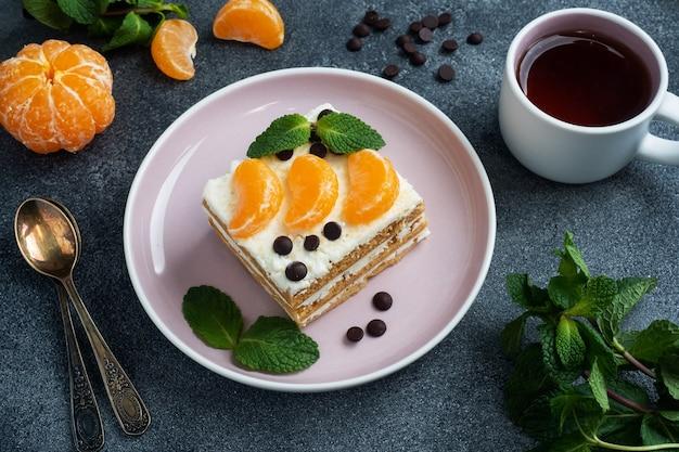 Lagen van biscuitgebak met botercrème, versierd met plakjes mandarijnchocolade en munt