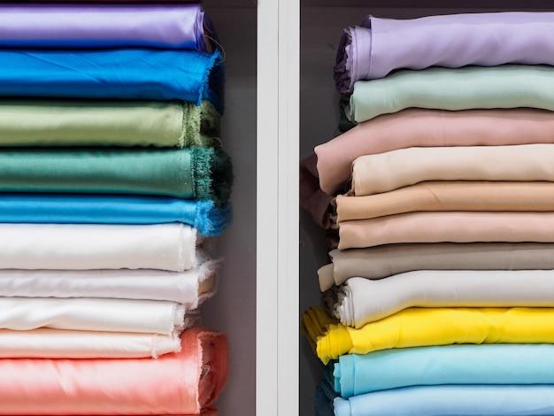Lagen van prachtige zijde en satijn stof in pastelkleuren in een winkel of fabriek, close-up.