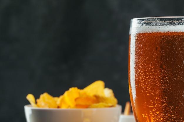 Lagerbier en snacks op stenen tafel.