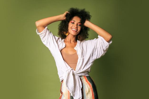 Laighing zwarte vrouw dansen en plezier maken. feeststemming. stijlvolle accessoires.