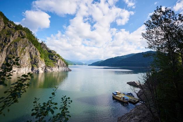 Lake vidraru, een kunstmatig meer in roemenië in de bergen van fagaras. blauwe lucht met wolken erboven