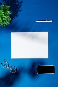 Lakens, gadgets en uitrustingsstukken op een blauwe tafel binnenshuis. creatieve, gezellige werkplek op kantoor aan huis, inspirerende mock-up met plantschaduwen op het oppervlak. concept van extern kantoor, freelance, sfeer.