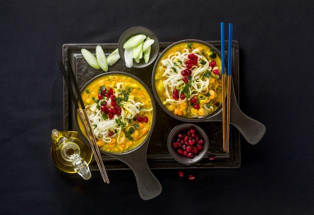 Laks met pompoen en kokosmelk, rijstnoedels, broccoli en granaatappelpitjes