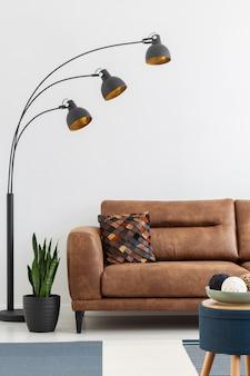 Lamp en plant naast bruin leren bank met kussen in wit loft interieur met kruk. echte foto
