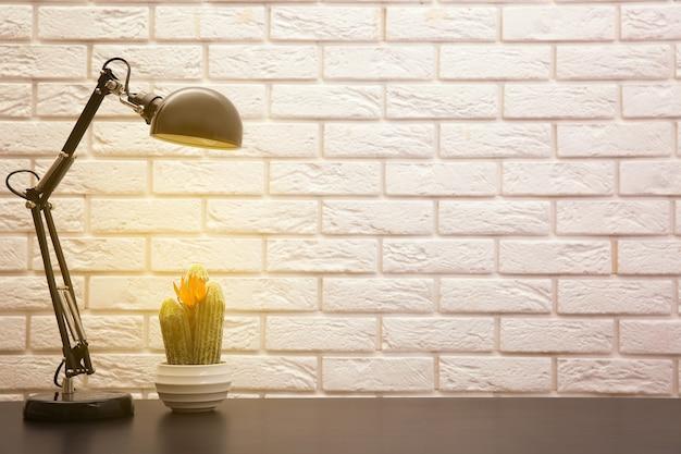 Lamp en plant op het bureau op muurachtergrond