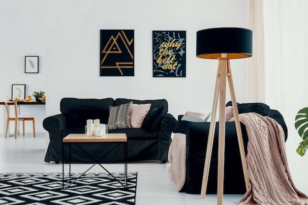 Lamp naast donkere bank met roze deken in wit plat interieur met posters en tapijt. echte foto