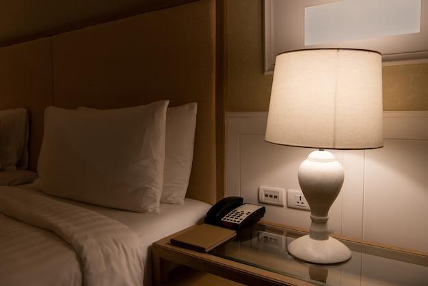 Lamp op een nachtkastje naast klassiek bed.