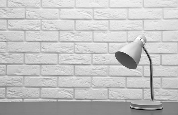 Lamp op het bureau op bakstenen muurachtergrond