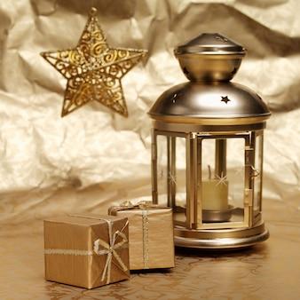 Lamp van kaarsen, geschenken en ster op gerimpelde gouden papieren achtergrond