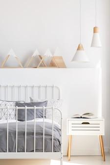 Lampen boven nachtkastje naast bed in wit kinderkamerinterieur met driehoeken. echte foto