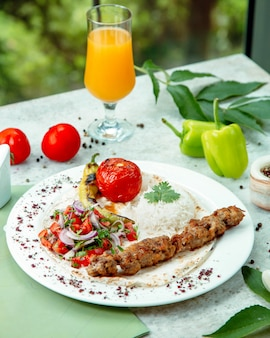 Lamskebab geserveerd met rijst, tomaat, komkommer en uiensalade, gegrilde groenten