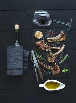 Lamsrack met knoflook, rozemarijn, specerijen op leisteenblad, wijnglas, olie in een schotel en fles over zwart houten oppervlak