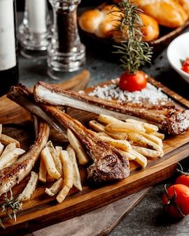 Lamsribben kebab geserveerd met franse vuren op een houten bord