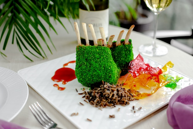 Lamsribbetjes bedekt met groene kokos hagelslag geserveerd met thaise rijst