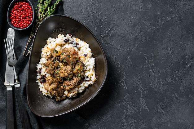 Lamsstoofpot in griekse stijl in een tomaat, met rijst. zwarte achtergrond.