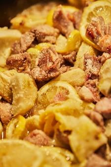 Lamsvlees met citroen, artisjokken en korianderstengels worden op laag vuur in een ketel gebakken.