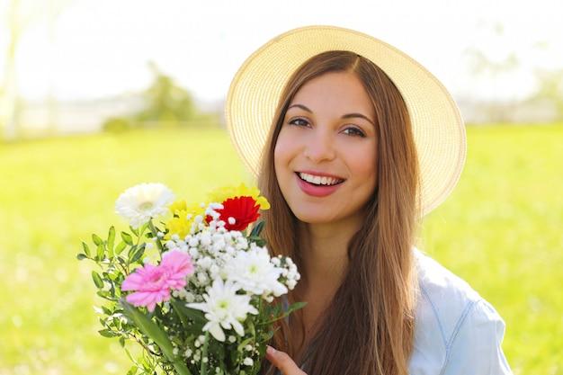 Land meisje met bos bloemen in velden
