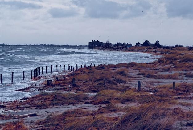 Land met veel struiken bij de zee onder een bewolkte hemel