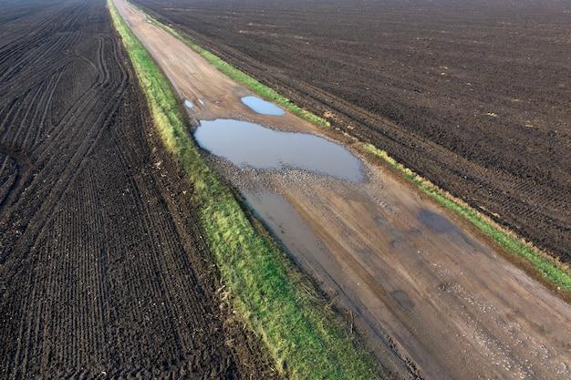 Land onverharde weg in een veld met plassen. lege landbouwgrond aan beide kanten van de weg.