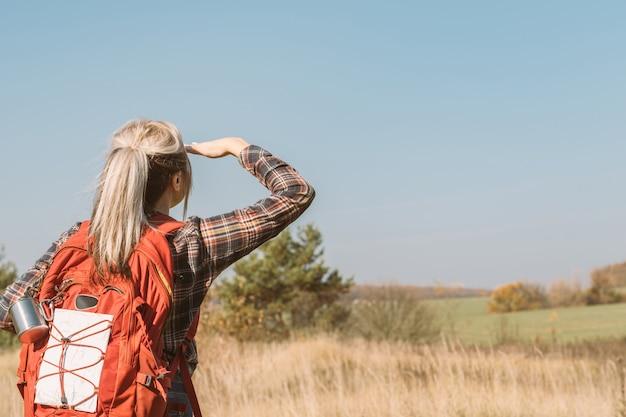 Land reizen achteraanzicht van dame wandelen met rugzak blauwe lucht en herfst weidelandschap