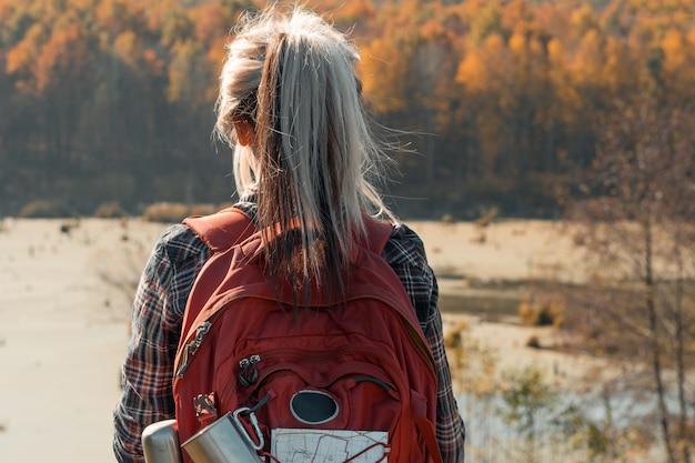 Land reizen achteraanzicht van dame wandelen met rugzak herfst natuur landschap