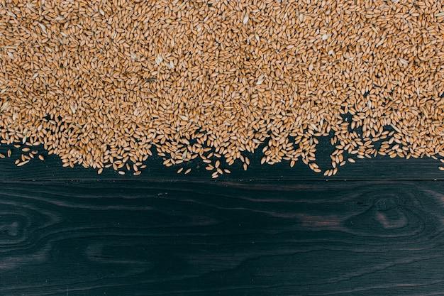 Landbouw achtergrond. tarwekorrels op donkere houten lijst