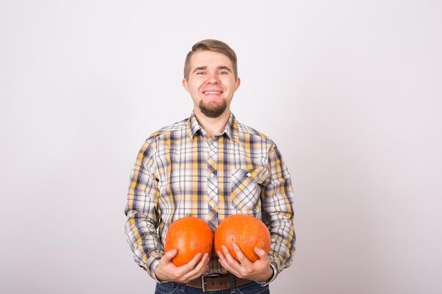 Landbouw herfst mensen concept jonge man boer met twee pompoenen en lachend op witte achtergrond