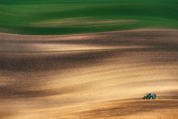 Landbouw kleine blauwe tractor die bruin lente veld ploegt en bespuit