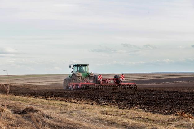 Landbouw, tractor die land met zaaibedcultivator voorbereidt als onderdeel van pre-zaai-activiteiten in het vroege lenteseizoen van landbouwwerkzaamheden op landbouwgronden.