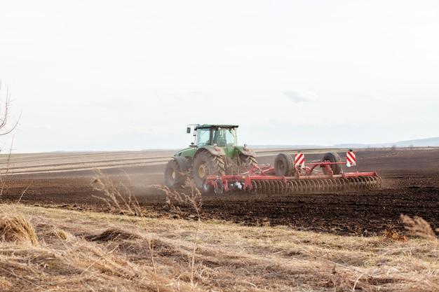 Landbouw, tractor die land voorbereidt met zaaibedcultivator als onderdeel van pre-zaai-activiteiten in het vroege voorjaar van landbouwwerkzaamheden op landbouwgronden.