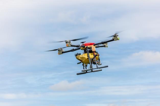 Landbouwdrones glijden boven rijstvelden en sproeien kunstmest. boeren gebruikten een drone om mest op rijstvelden te spuiten. landbouw technologie concept