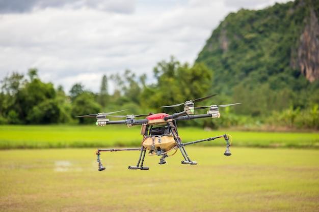 Landbouwdrones vliegen over rijstvelden om kunstmest te strooien, hoge resolutie foto's van industriële drones die chemicaliën sproeien op rijstvelden en velden