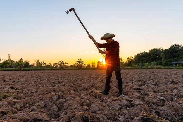 Landbouwer die aan gebied bij zonsondergang werkt openlucht