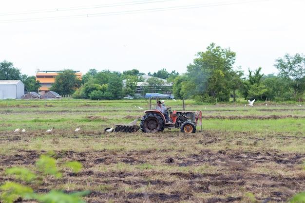 Landbouwer die in tractor land met zaaibedlandbouwer voorbereidt