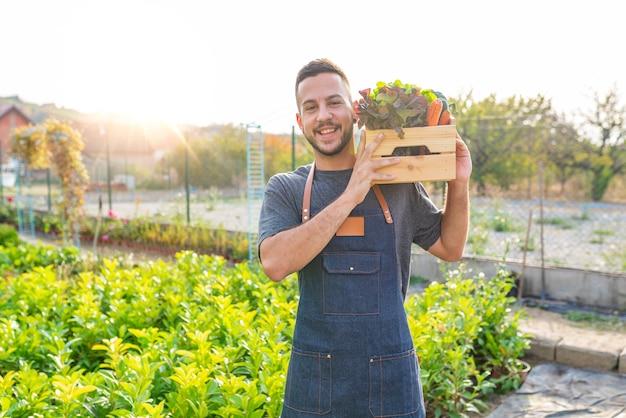 Landbouwer die in zijn handen houten doos met lokale vegitables houdt.