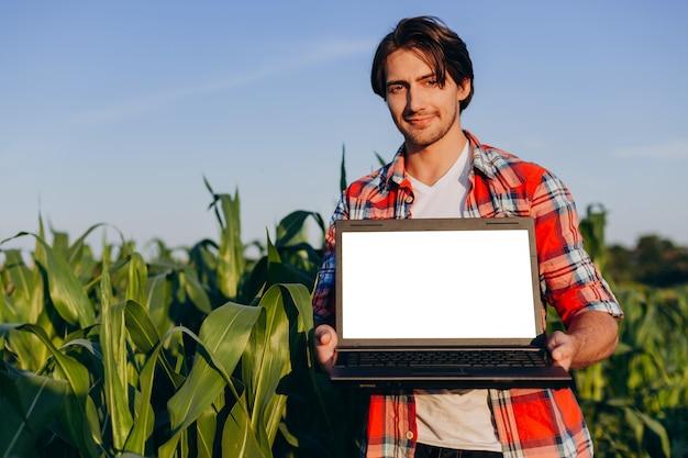 Landbouwer die zich op een gebied bevindt dat open laptop houdt. wit scherm mockup